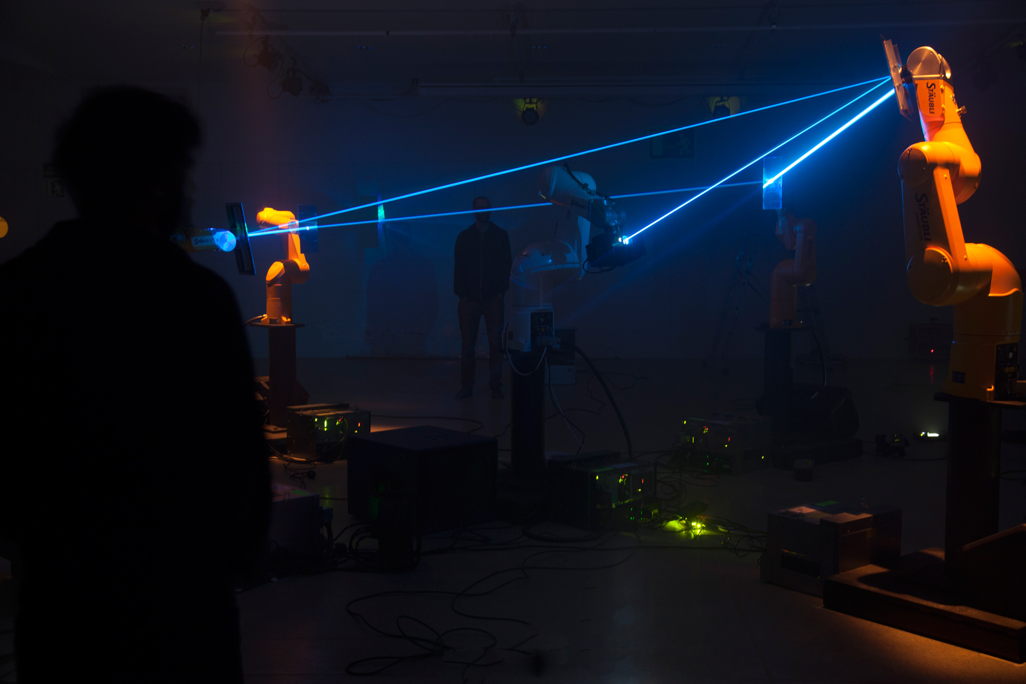 Robotic arms playing with a laser beam in front of the audience.